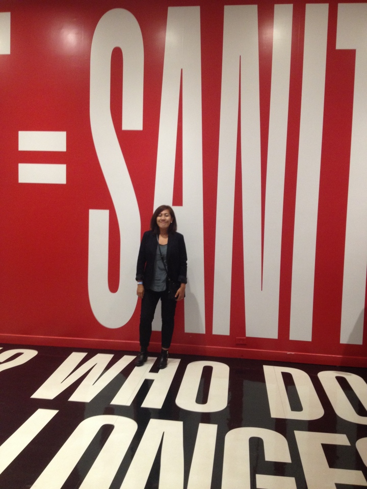 A beautiful woman at the Hirhhorn standing in front a wall that reads 'Sanity'